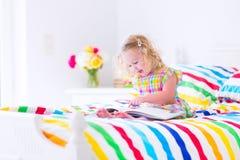 Liten flicka som läser en bok i säng Arkivfoto