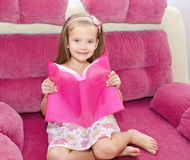 Liten flicka som läser en bok och placerar på soffan royaltyfri foto