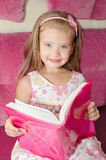 Liten flicka som läser en bok och placerar på soffan arkivbild
