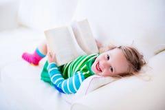 Liten flicka som läser en bok på en vit soffa royaltyfri fotografi