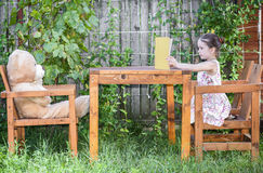 Liten flicka som läser en bok till hennes leksakbjörn Arkivfoton