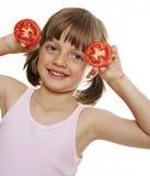 Liten flicka som leker med en tomat Arkivfoto