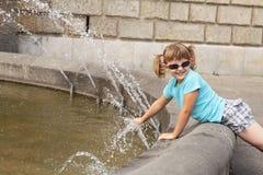Liten flicka som leker med vatten - springbrunnen Arkivfoton
