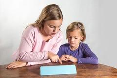 Liten flicka som leker på en beräknande apparat för tablet Fotografering för Bildbyråer