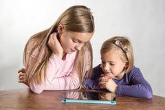 Liten flicka som leker på en beräknande apparat för tablet Arkivfoto