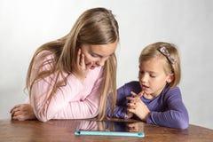 Liten flicka som leker på en beräknande apparat för tablet Arkivbilder
