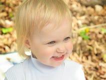Liten flicka som ler i en parkera om den soliga dagen arkivfoto