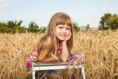 Liten flicka som ler i vetefältet på en varm sommardag Arkivfoto