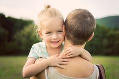 Liten flicka som ler och kramar hennes moder arkivbild
