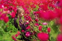 Liten flicka som ler och trycker på huvud av härliga livliga blommor, medan sitta, i att blomma trädgården arkivbilder
