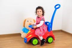 Liten flicka som ler på en leksakbil Arkivfoton