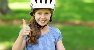 Liten flicka som ler på kameran på en rosa cykel stock video