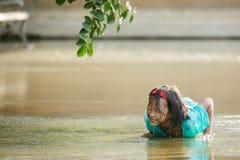 Liten flicka som ligger i en pöl Arkivfoton