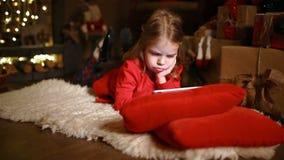 Liten flicka som ligger i matta med gåvor runt om att använda på minnestavlan lager videofilmer