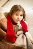 Liten flicka som ligger i säng- och innehavtermometer i mun Arkivbild