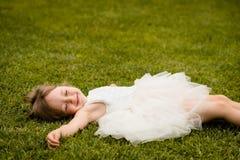 Liten flicka som ligger på att le för gräsgräsmatta arkivfoto