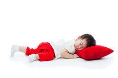 Liten flicka som ligger på den röda kudden Arkivbild