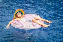 Liten flicka som ligger på den uppblåsbara rubber cirkeln Royaltyfri Foto