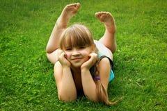 Liten flicka som ligger på gräs Royaltyfria Bilder
