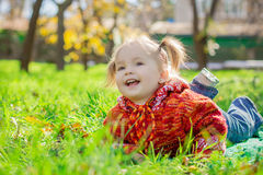 Liten flicka som ligger på gräset i parkera Arkivbilder