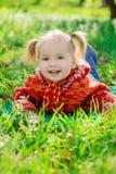 Liten flicka som ligger på gräset i parkera Fotografering för Bildbyråer