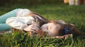 Liten flicka som ligger på grönt gräs och kramar en brun kanin lager videofilmer