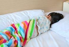 Liten flicka som ligger på sängen med filten fotografering för bildbyråer