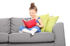Liten flicka som läser en placerad bok på soffan Royaltyfri Fotografi