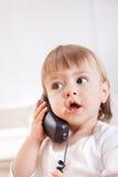 Liten flicka som lyssnar till en telefon Arkivfoto