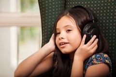 Liten flicka som lyssnar till musik Arkivfoto