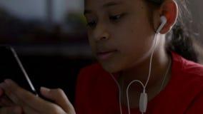 Liten flicka som lyssnar till musik fr?n mobiltelefonen