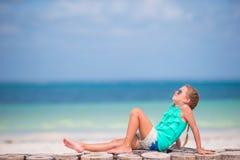 Liten flicka som lyssnar till musik på hörlurar på stranden royaltyfria bilder