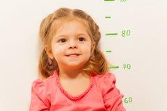 Liten flicka som mäter höjd mot väggen i rum Royaltyfri Bild