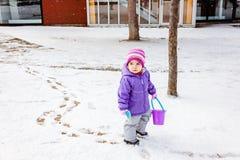 Liten flicka som man årigt spela utanför i vinter parkerar och att lämna, spårar på snön C Royaltyfri Foto