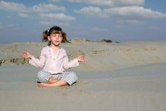 Liten flicka som mediterar i öken Arkivbild