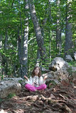Liten flicka som mediterar i skogen Royaltyfria Bilder