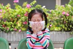 Liten flicka som nyser på näsa med silkespapperpapper, medan utomhus- arkivfoto