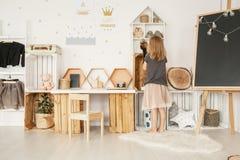 Liten flicka som in organiserar hennes leksaker i det vita nordiska stilsovrummet Arkivbilder