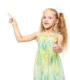 Liten flicka som pekar fingret på en vit bakgrund Arkivbild