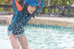 Liten flicka som plaskar vatten i simbassäng arkivbilder