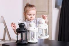 Liten flicka som poserar i serie av tre lampor med stearinljus på tabl Royaltyfri Fotografi