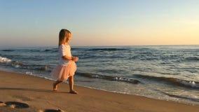 Liten flicka som promenerar stranden lager videofilmer