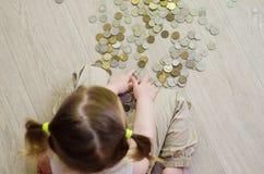 Liten flicka som räknar och spelar med mynt royaltyfri fotografi