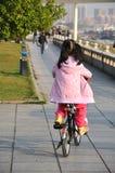 Liten flicka som rider en cykel Arkivfoto