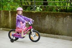 Liten flicka som rider en cykel Royaltyfria Foton