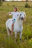 Liten flicka som rider en häst Arkivbild