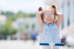 Liten flicka som rider en sparkcykel i staden Arkivfoto