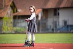 Liten flicka som rider en sparkcykel på en sportlätthet Arkivfoto
