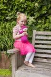 Liten flicka som rymmer den hemlagade virkningdockan i trädgården Royaltyfria Bilder