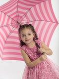 Liten flicka som rymmer det stora randiga paraplyet arkivfoto